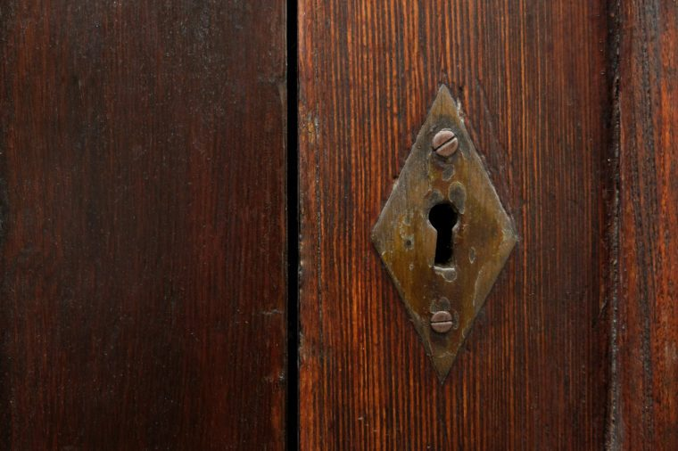 Keyhole in old wooden door, copy space on one side.