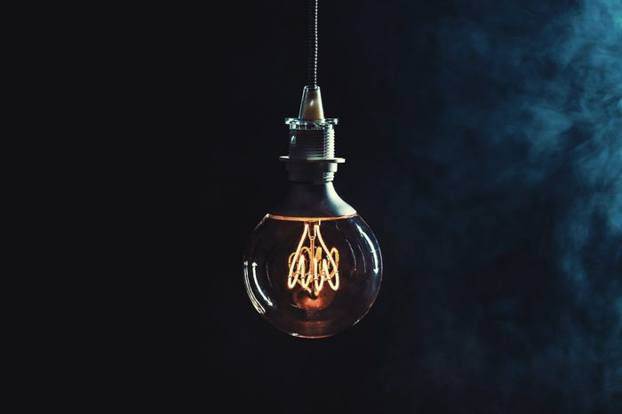 Vintage lightbulb on dark background with bright yellow shining wire