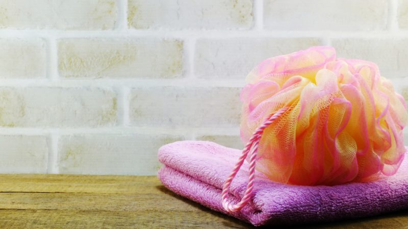 plastic bath puff shower and towel on a wooden background