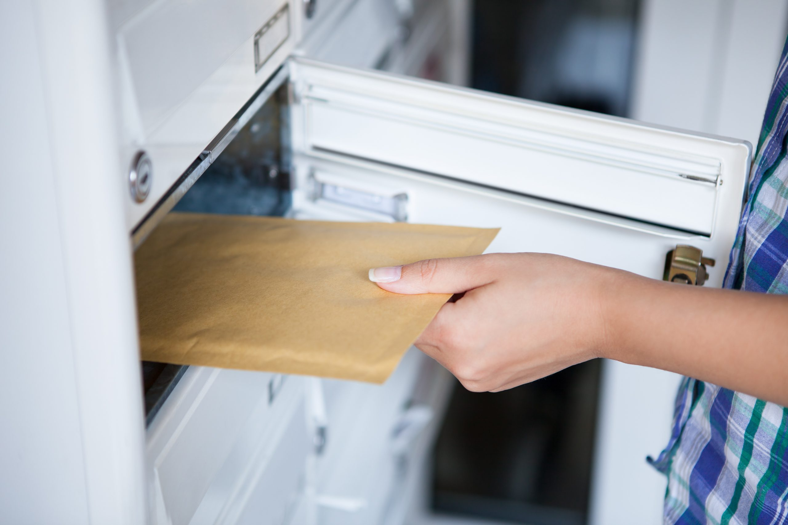 Close-up of woman's hand pulling envelop from mailbox