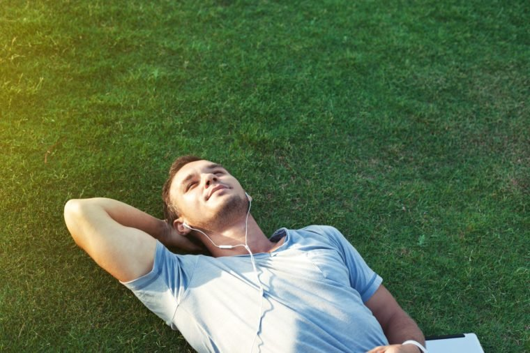 young man on the grass listening music on tablet