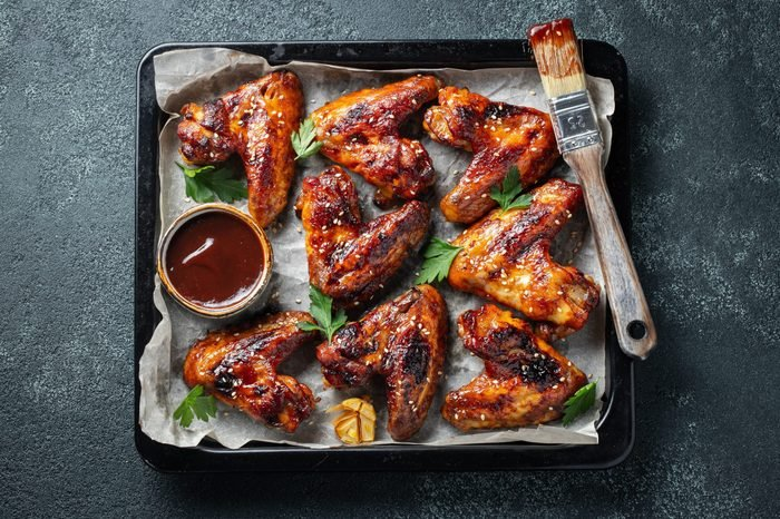 Roasted chicken wings in barbecue sauce with sesame seeds and parsley in a baking tray on a dark table. Top view. Tasty snack for beer on a dark background. Flat lay.