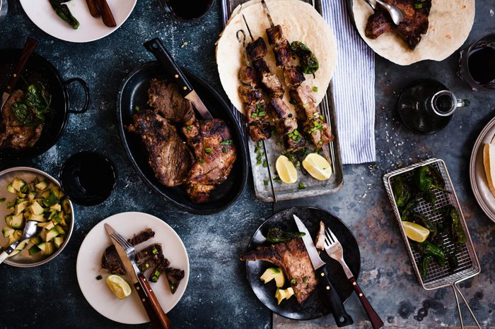 Grilled variety meats and skewers and vegetables serving on party table. Pork and beef grilled meat. Overhead of party outdoor table with grilled variety meat.