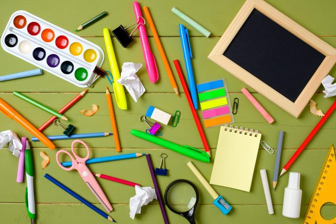 Messy and cluttered kids desk with school supplies. Education, studying and back to school concept. Child desk top view, copy space, flat lay composition.