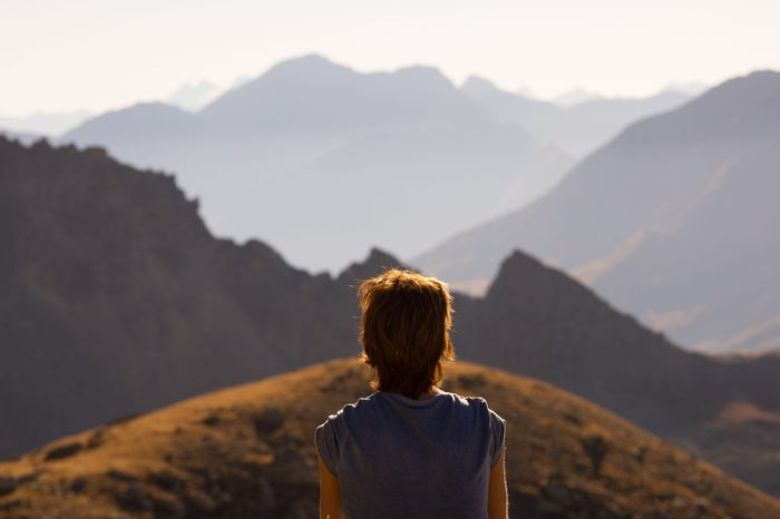 One person looking at view high up on the Alps. Expasive landscape, idyllic view at sunset. Rear view.