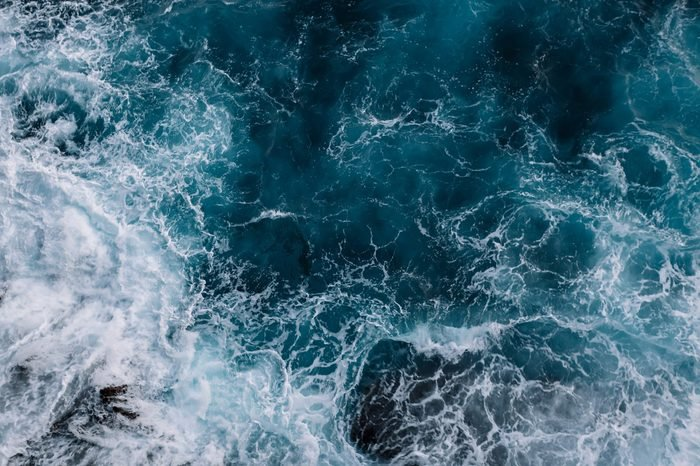 Aerial view to ocean waves. Blue water background