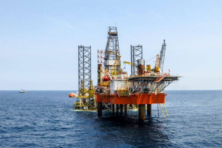 Drilling rig is installed side by side to production oil platform in offshore oil and gas field.