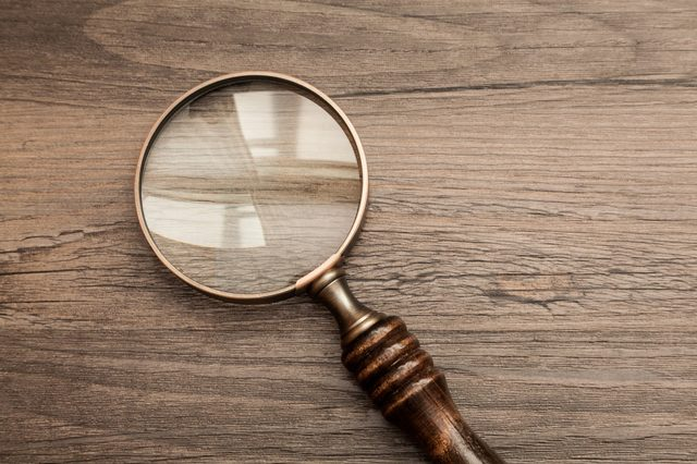 Old fashioned magnifying glass on a dark wood background