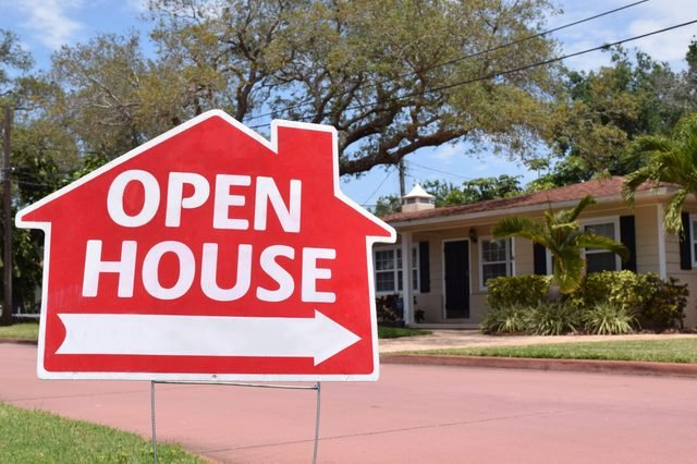 Bright red open house real estate sign in nice suburban neighborhood, sunny day.