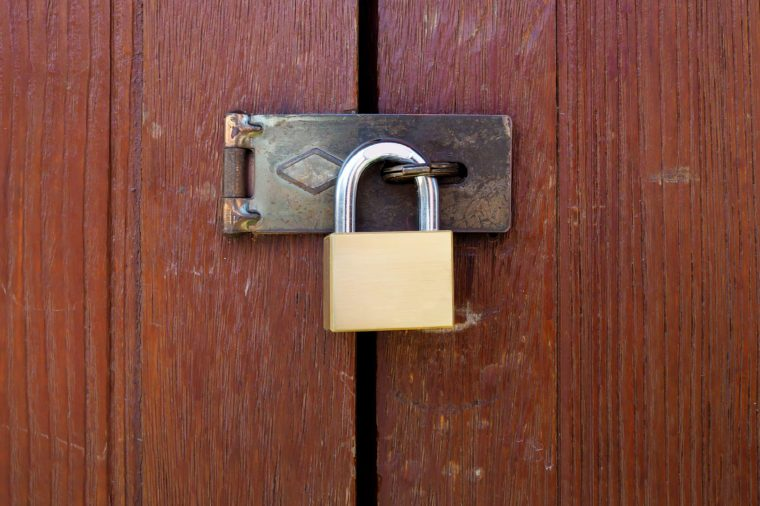 Locked padlock with chain at wooden door background, vintage, Closeup