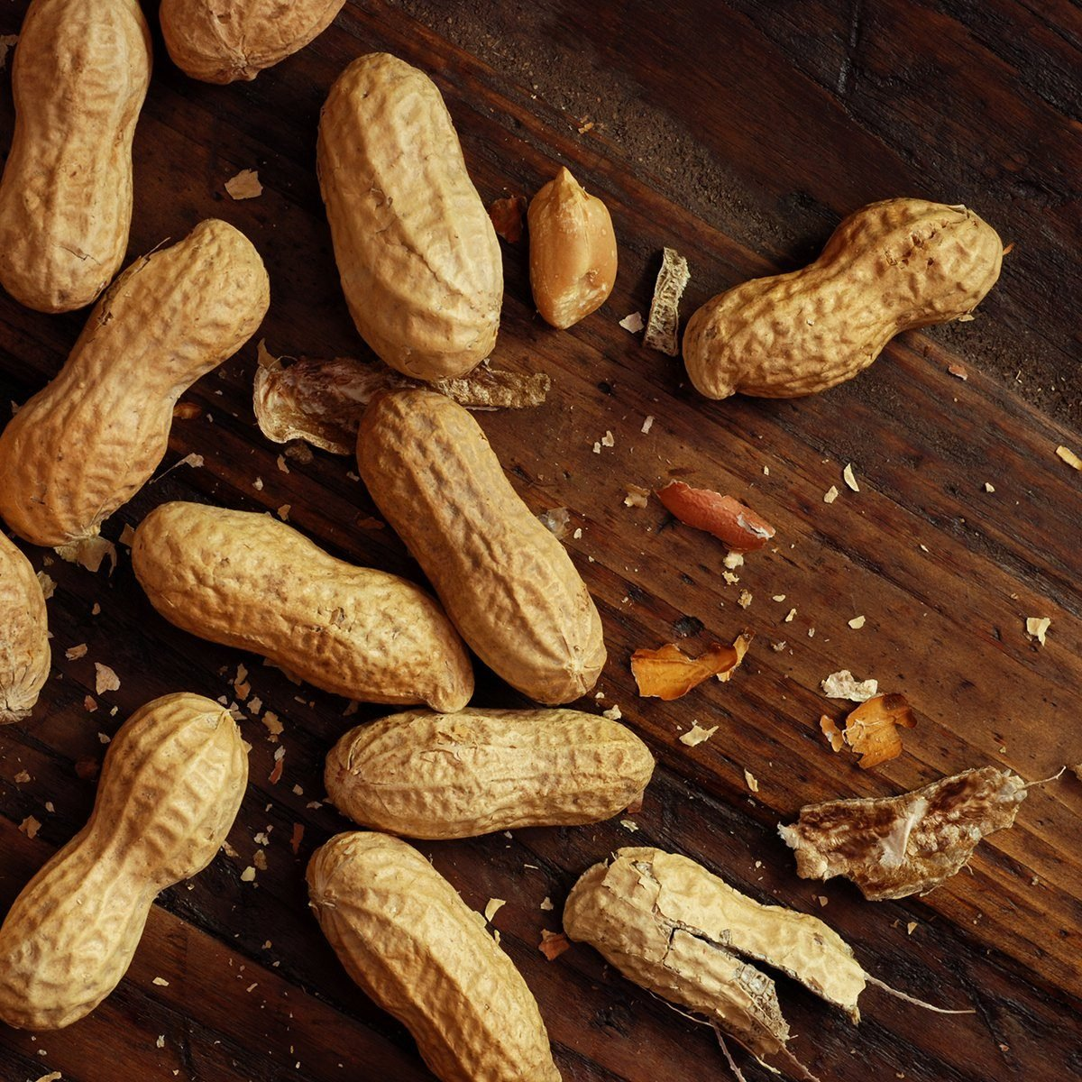 Roasted peanuts with broken shells and pieces scattered on rustic, dark wood background.