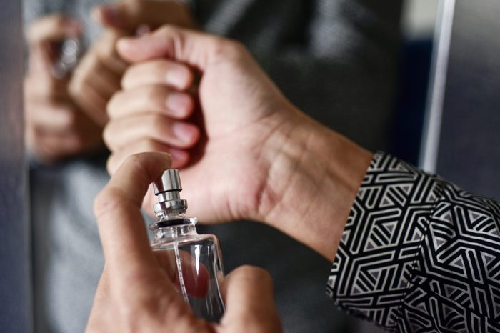 closeup of a young caucasian man spraying perfume on his wrists