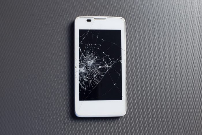 broken phone, modern touch screen smartphone with broken screen, on gray background.