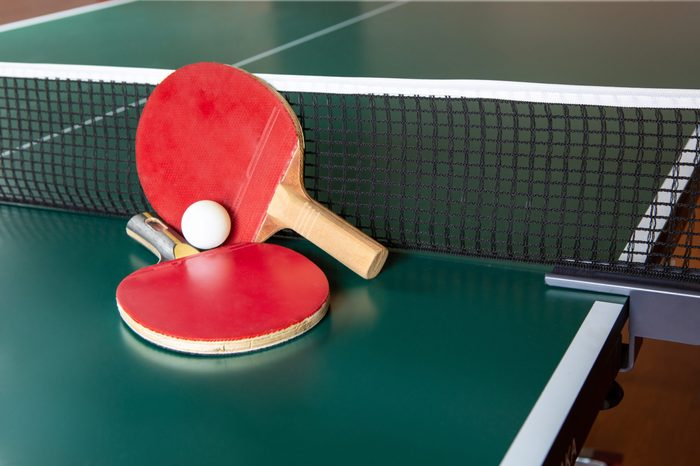 Two ping-pong rackets and a ball on a green table. Close-up, ping-pong net.