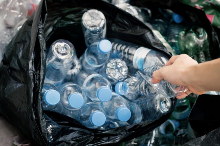hand holding plastic bottle to dispose in black garbage bag, waste management and plastic recycle concept.