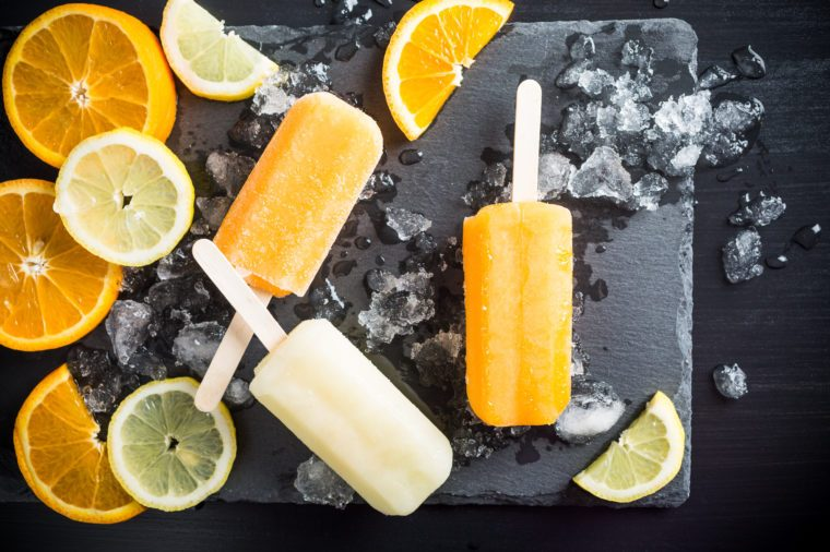 Homemade orange and lemon popsicles with ice and citrus fruits on stone black background. Summer food concept. Top view.