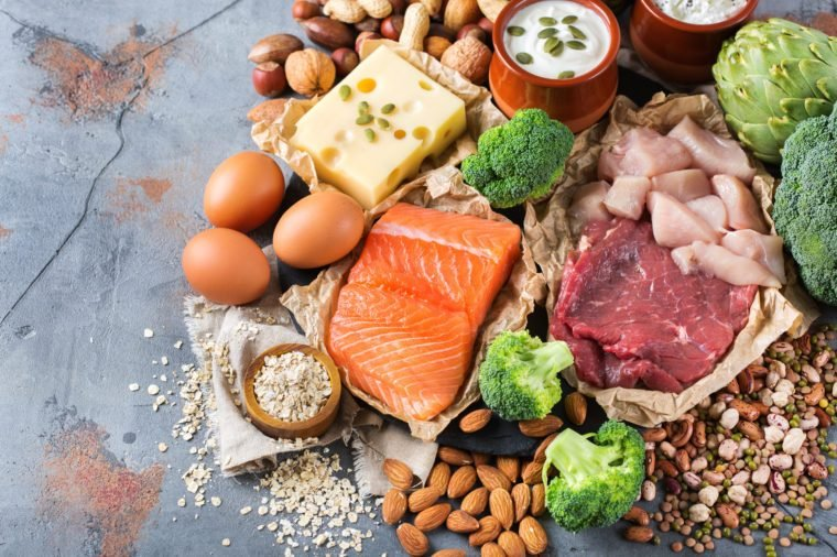 Assortment of healthy protein source and body building food. Meat beef salmon chicken breast eggs dairy products cheese yogurt beans artichokes broccoli nuts oat meal. Top view flat lay