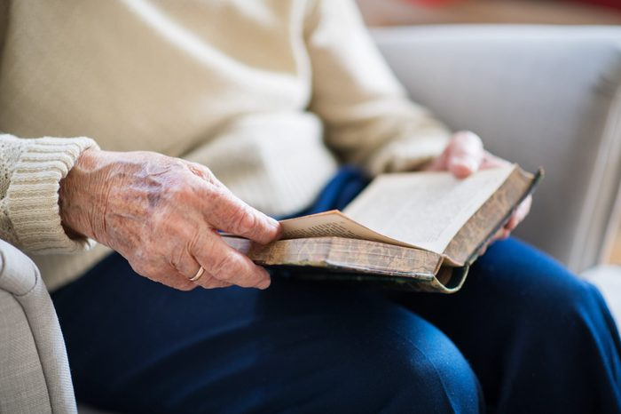A senior woman reading Bible at home at Christmas time.