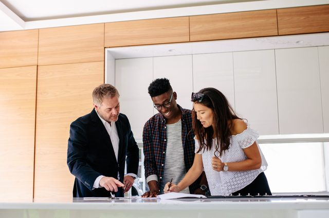 Couple signing a contract documents while standing inside a house with real estate agent. Interracial couple with realtor signing mortgage contract.