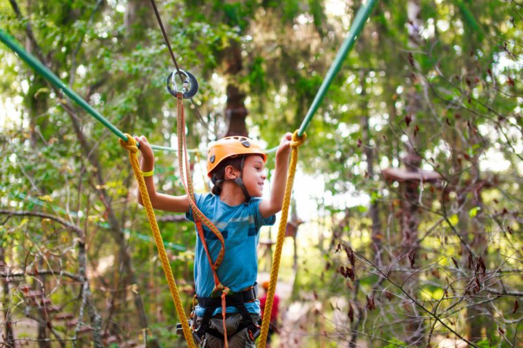 boy passes a rope obstacle course in the forest. cheerful child bravely overcomes extreme rope route outdoors. zip line