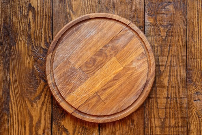 Wooden round empty board for pizza on wood table background, top view. Mockup for menu, recipe or any dish. Vertical image