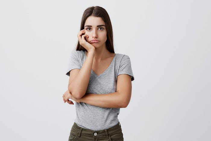 Portrait of young sad charming caucasian female student with dark long hair in stylish gray outfit holding head with hand, looking in camera with unhappy expression after receiving bad mark on exam