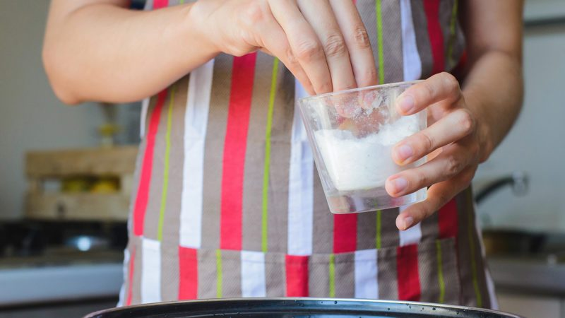 Cook takes cup of salt to water in bowl