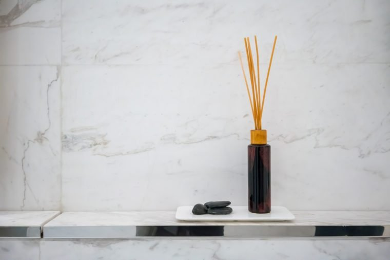 Scented diffuser stick in black glass bottle against white marble wall background for decoration in luxury bathroom.