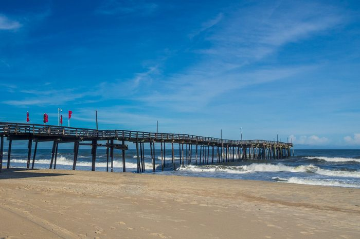 Old wood fishing pier at the sandy beach