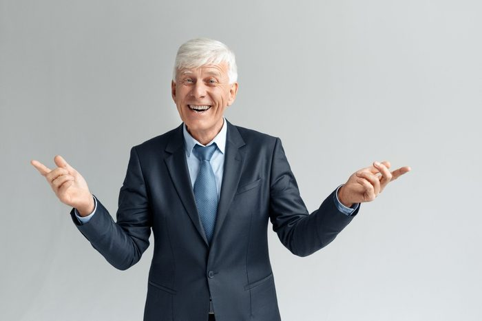 Senior business man studio standing isolated on gray wall hands aside looking camra laughing playful