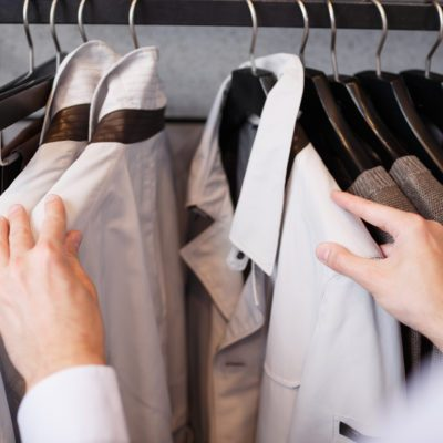 Business shopping, close-up of man choosing shirt at showcase in clothing mall or fashion boutique, wardrobe, point of view shot