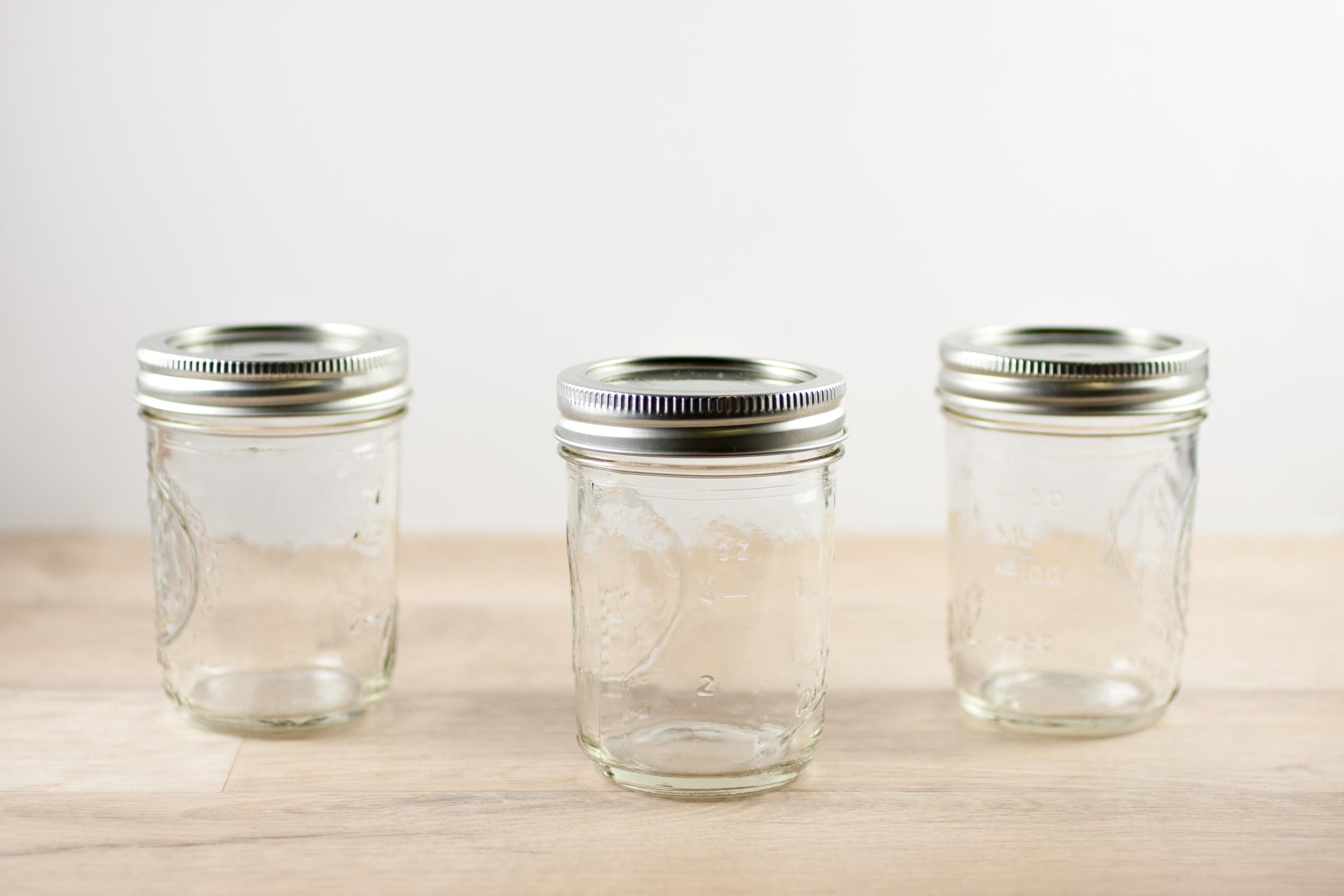 Empty canning jars sit on a wooden table.