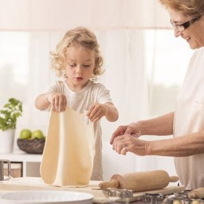 Bright kitchen interior with child making the cake with her smiling grandma