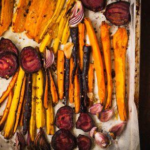 Roasted vegetables on a baking pan. Varieties carrots, beetroot, butternut squash sliced in baking pan. Vegetarian, diet, eating food concept.