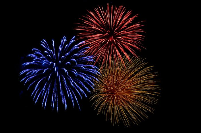 three colorful firework explosions on a black sky