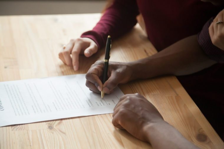 African american man signing contract, black man hand putting signature on official document, biracial clients customers couple make purchase or sign prenuptial agreement concept, close up view