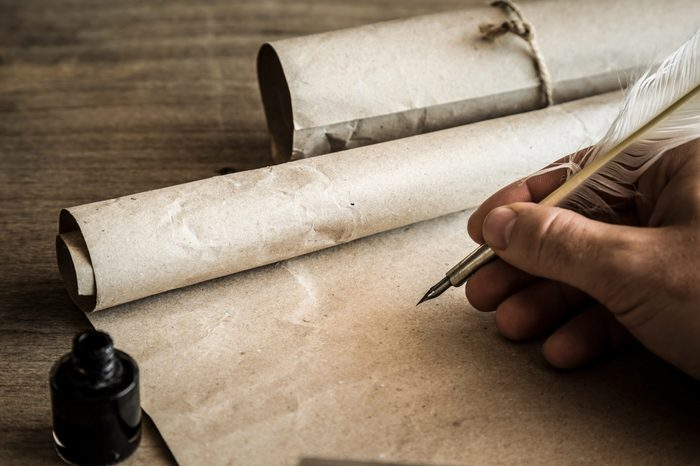 Hand writing with old quill pen on the old paper. Historical atmosphere. Empty place for a text.