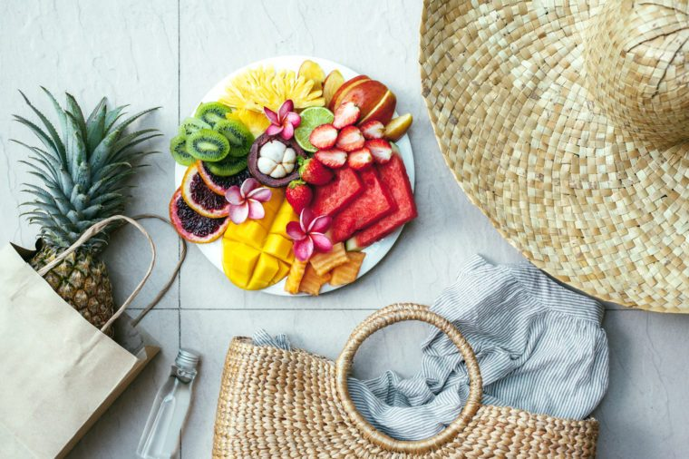 Fresh fruit plate and set of summer fashion beach accessories, top view from above (overhead). Tropical beach lifestyle.