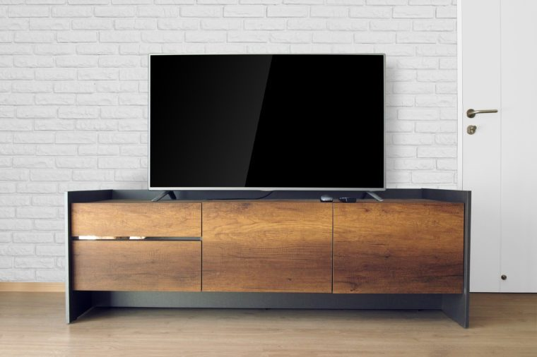 Led TV on TV stand in empty room with white brick wall. decorate in loft style.