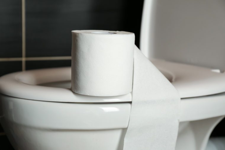 Roll of paper on toilet bowl in restroom