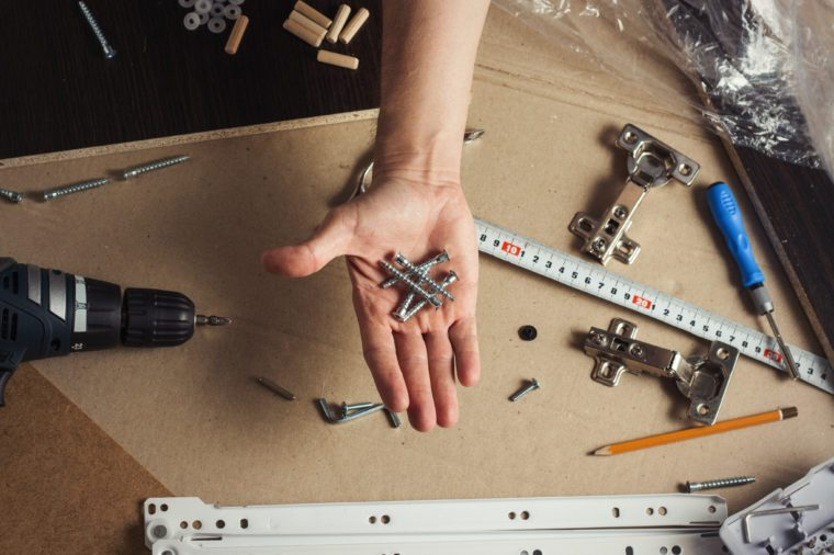 man's hand with tools for building furniture. Flat lay, top view.