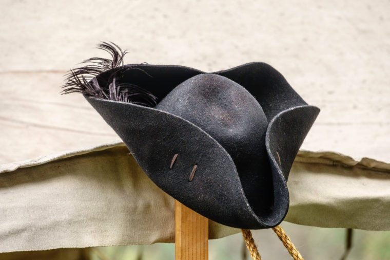 Feathered black felt hat, for man or woman, on tentpole in a military camp at a reenactment of the American Revolutionary War (1775-1783)