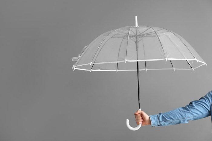 Female hand with stylish umbrella on grey background