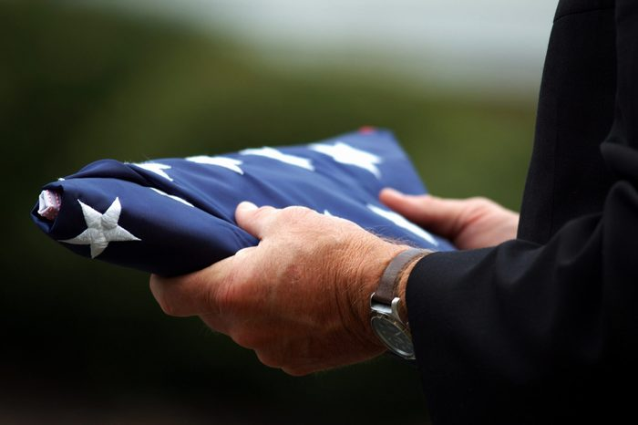 Man's hands holding a folded American flag