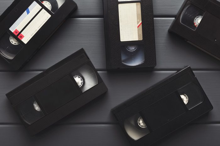 Retro video cassettes on gray wooden background. Top view on front sides. Back to the past and multimedia concept, copy space, flat lay