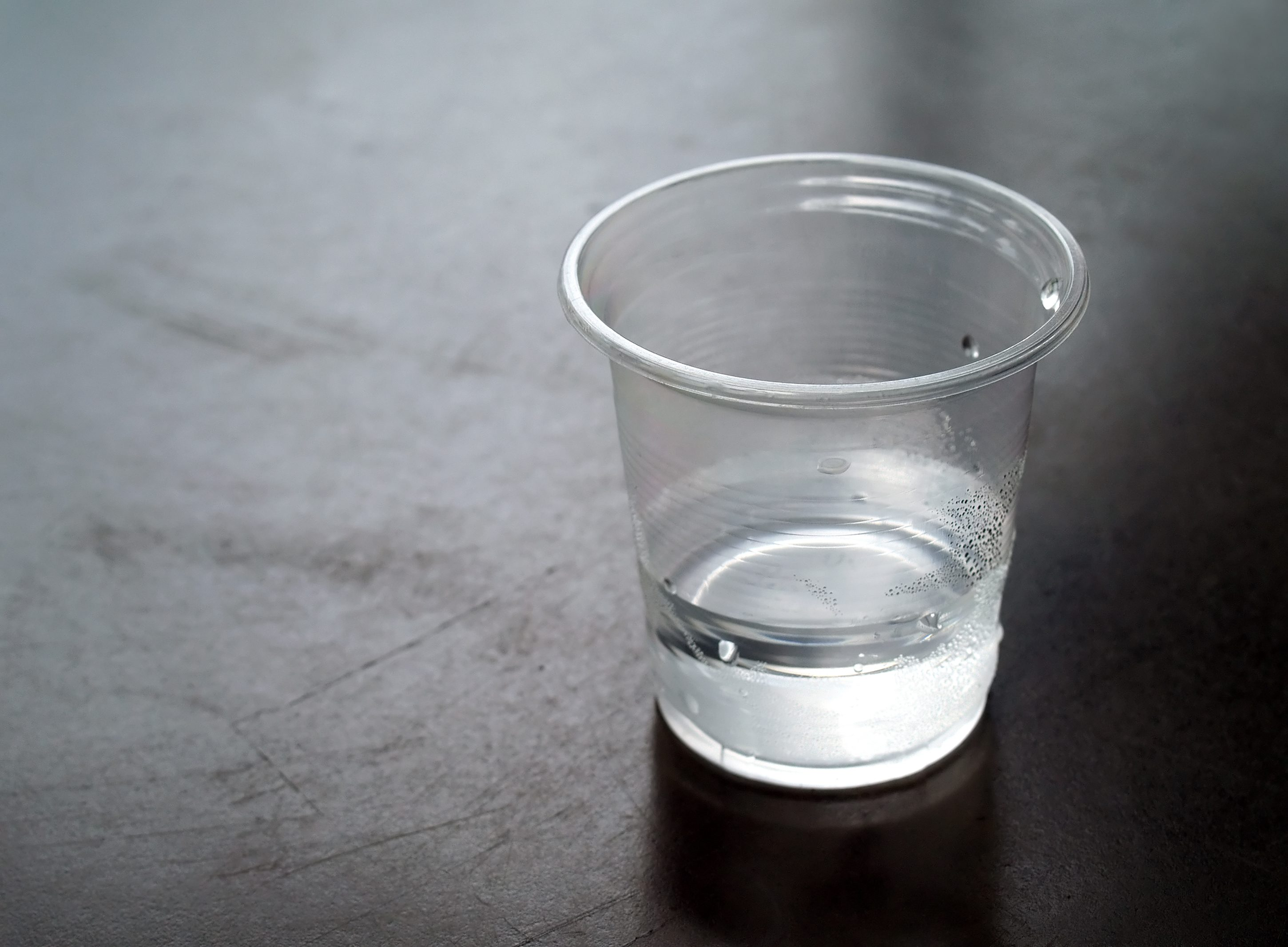 close-up few water in transparent plastic cup with water drops on dark brown metal table with copy space, dark tone image, selective focus