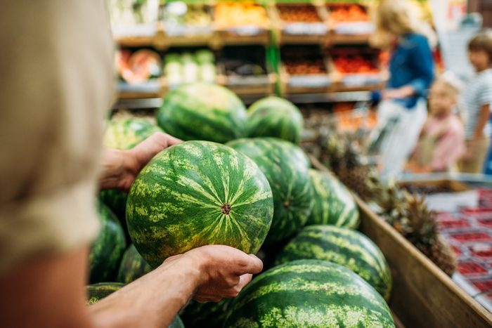 partial view of woman picking watermelon in grocery shop