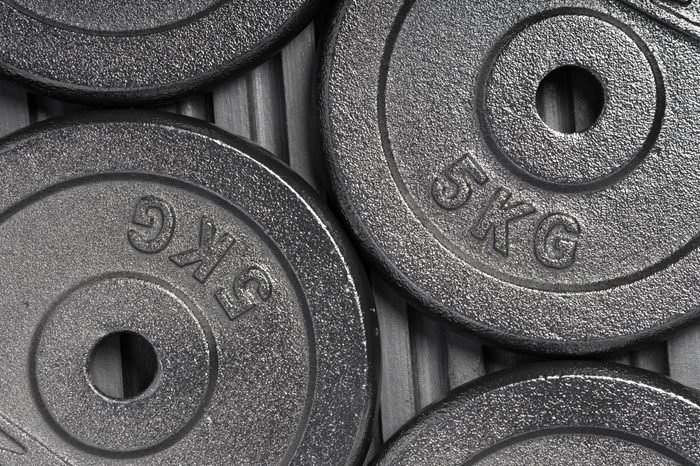 Weight plates on a black rubber floor inside a weight training gym / fitness studio