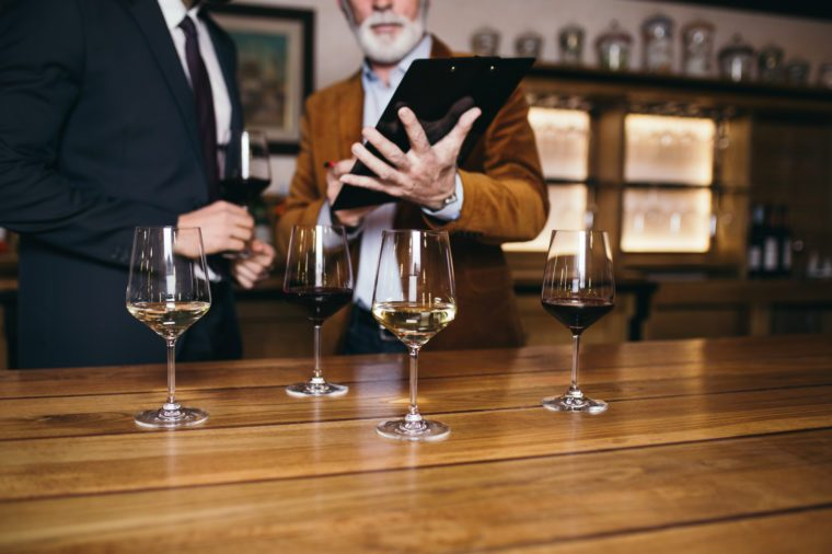Winemakers in wine cellar holding glass of wine and checking it. Sommeliers testing wines in winery.