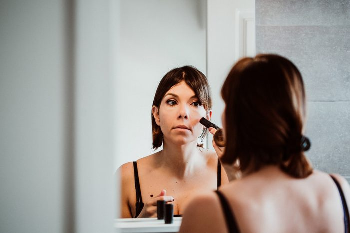 Young and pretty short-haired woman putting on makeup in front of the mirror in her house in the morning. Lifestyle.